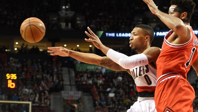 Portland Trail Blazers guard Damian Lillard (0) passes the ball on Chicago Bulls guard Derrick Rose (1) during the first quarter of an NBA basketball game in Portland, Ore., Tuesday, Nov 24, 2015.