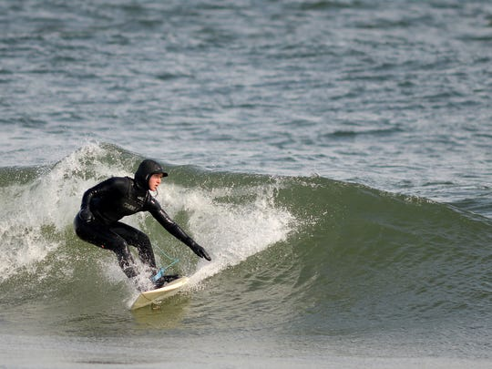 """Laurel Harrington rides a winter wave near 41st Street. """"When you fall under, it's like a brain freeze,"""" Harrington says of winter surfing. """"It can cut through your suit."""""""