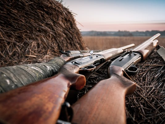 Hunting shotguns on haystack during sunrise in expectation of hunt