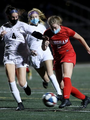 Hingham's Ava Maguire rockets a shot on goal while Whitman-Hanson's Makenna Marshall tries to get back on defense.
