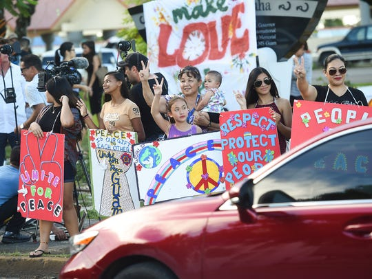 Guam residents wave to motorists during a peace rally