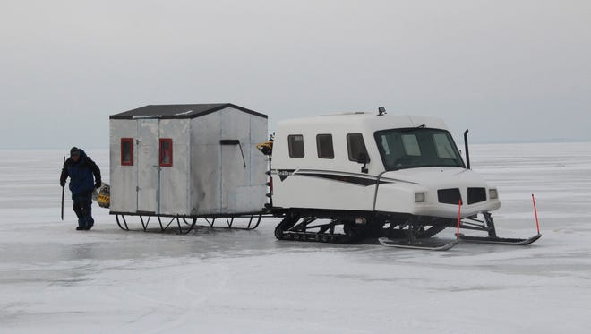 Lance Sweeting of Oshkosh, an assistant guide with Larry Smith Outdoors, works to set up a shanty pulled into place with a SnoBear tracked vehicle on Petenwell Lake on Jan. 14, 2016.