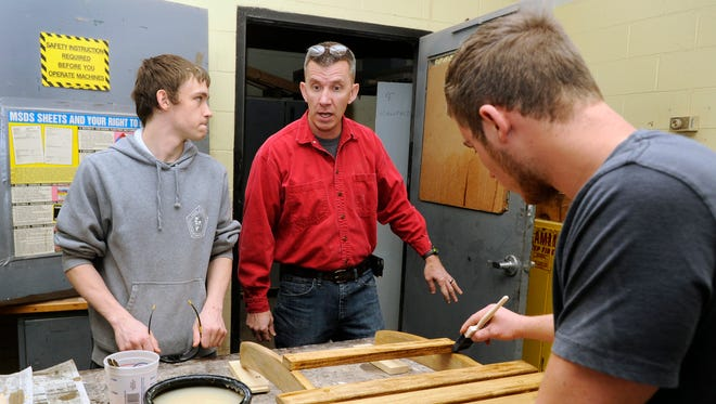 Lancaster High School teacher Andy Phillips, center, works with his senior class students. Phillips won the 2014 Mary Good Award from the United Way.
