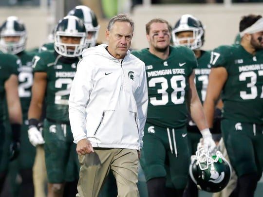 Michigan State head coach Mark Dantonio and team walk off the field after a storm warning was issued during the first half of an NCAA college football game against Penn State, Saturday, Nov. 4, 2017, in East Lansing, Mich. (AP Photo/Carlos Osorio)