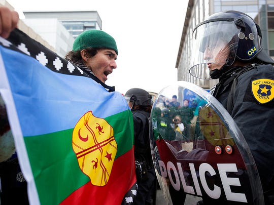 Anthony Fierro yells in front of a police officer as protesters are stopped from marching up State Street during President Donald Trump's announcement to eliminate vast portions of Utah's Bears Ears and Grand Staircase-Escalante national monuments in Salt Lake City, Utah, on Monday, Dec. 4, 2017.