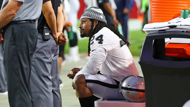 Aug 12, 2017; Glendale, AZ, USA;  Oakland Raiders running back Marshawn Lynch sits on a cooler on the bench during the national anthem prior to the game against the Arizona Cardinals at University of Phoenix Stadium.