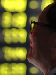 A man watches falling stock prices at a brokerage house
