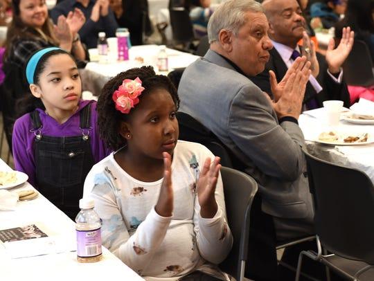 Novi Meadows'sixth-grader Taylor Weston, front applauds