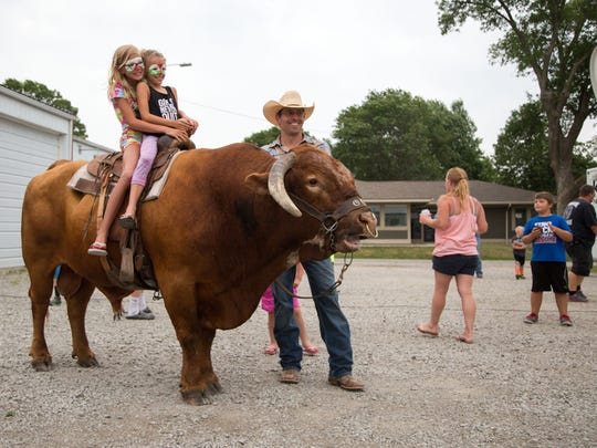 """Madison Anderson, front, 8 Mia Shanks, 10, get their picture taken on Jason Dent's bull Ole before Jason's first episode on this season of Big Brother.  Supporters packed the Humeston Fire Department to watch Jason, a rodeo clown who performs as """"Whistle-Nut"""" compete on Big Brother Wednesday, June 28, 2017."""