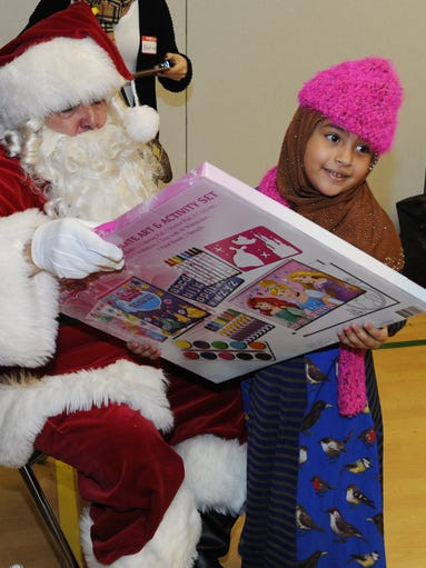 Santa gives first grader Malak Alguheim, 7, a Disney