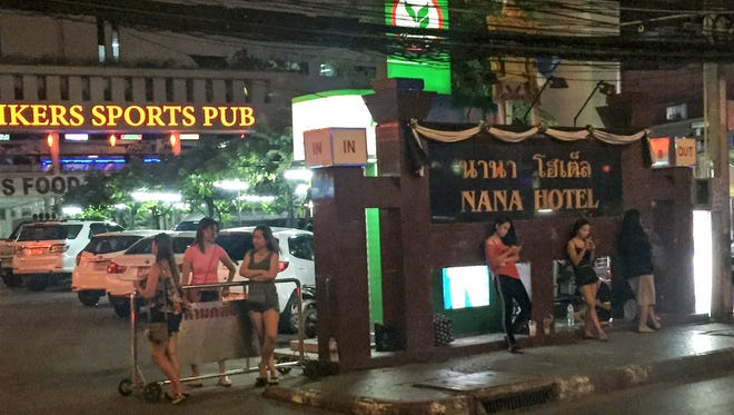 Women wait on the street in the Nana Plaza red light district in Bangkok, Thailand.
