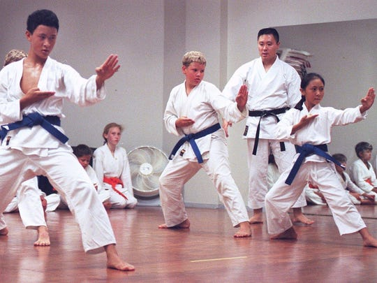 Sensei Sonny Kim (far right) watches in 1998 as his blue belt students practice their forward moves during a class.