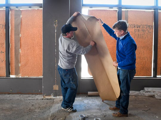 "Casey Todd (right) and Jason Todd cut paper to cover the first floor windows of the Historic Soaper Hotel during the renovations for a new restaurant called ""Hometown Roots"" that will open later this summer Thursday, April 26, 2018."