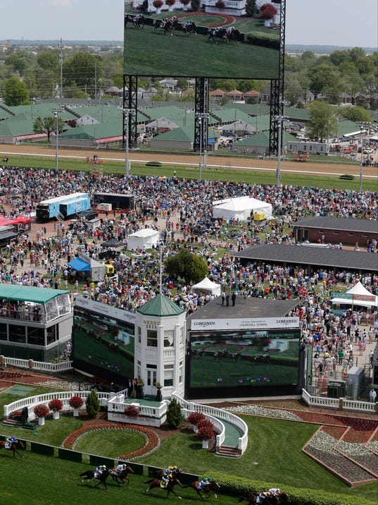 FILE - In this May 3, 2014, file photo, fans watch a race on a large video screen before the Kentucky Derby horse race at Churchill Downs in Louisville, Ky. A racehorse died Thursday, May 22, 2014, at Churchill Downs after a freak fall that the trainer blamed on the sound of a starting gate bell blaring on the track's new sound system. The 5-year-old mare Never Tell Lynda was walking toward the paddock on the dirt track when she reared, twisted and fell, hitting her head, said her trainer, Kenneth Wirth. Wirth later said the horse was spooked by what Wirth thinks was the sound of a starting gate bell coming from a commercial on Churchill's massive new video board. The system includes 750 speakers. (AP Photo/Charlie Riedel, File)