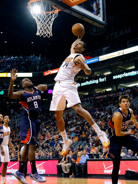 Phoenix Suns' Gerald Green (14) dunks over Atlanta Hawks' Shelvin Mack (8) and Kyle Korver during the second half of an NBA basketball game, Sunday, March 2, 2014, in Phoenix. The Suns won 129-120. (AP Photo/Matt York)