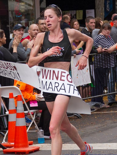 Morgan Burrows, of Corning, is the first female to cross the Wineglass Marathon finish line. The race was run from Bath to Corning, NY on Sunday morning, Oct. 12, 2013.
