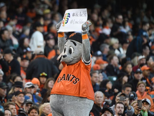 San Francisco Giants mascot Lou Seal holds up a sign