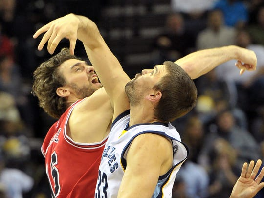 FILE - In this Dec. 19, 2014, file photo, Chicago Bulls forward Pau Gasol, left, and his brother Memphis Grizzlies center Marc Gasol vie for a jump ball at the start of an NBA basketball game in Memphis, Tenn. Pau and Marc Gasol will make history Sunday, Feb. 15, 2015, when the Spanish centers become the first brothers to start against each other in the NBA All-Star game. (AP Photo/Brandon Dill, File)