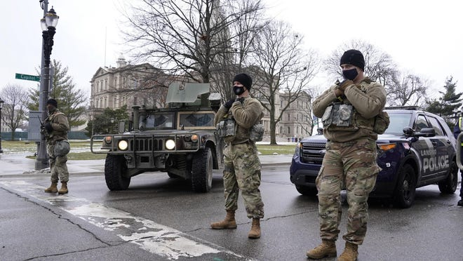 Michigan National Guard members stand at an intersection outside the state capitol in Lansing, Mich., Sunday, Jan. 17, 2021.