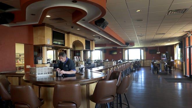 Bar manager Brian Siebers unpacks glasses at Calmes' Pub, the former Lazy Dog in Kaukauna.