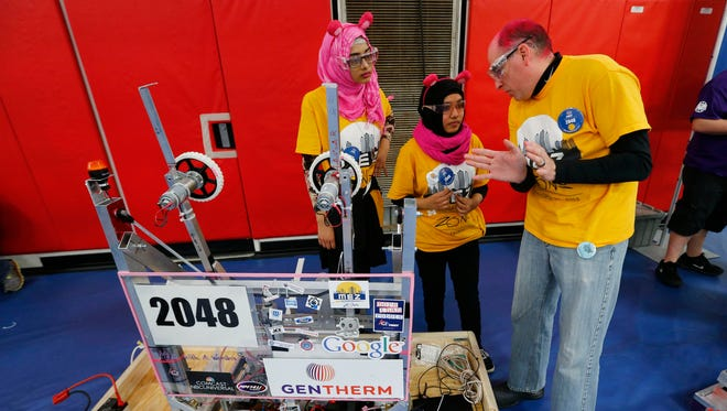 In this March 27, 2015 photo, Detroit International Academy for Young Women students Tunzzina Chowdhury, left, and Papia Aziz listen to Dennis Cabay, right, a team mentor, talks about their robot during the For Inspiration and Recognition of Science and Technology, FIRST, Robotics district competition in Livonia.