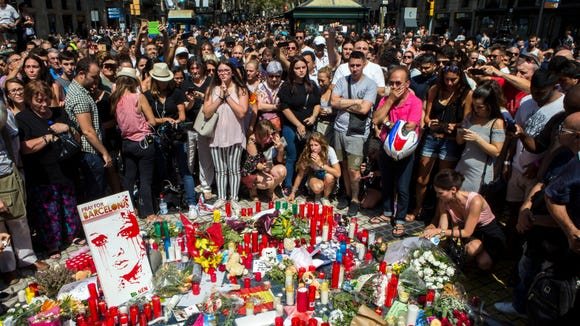 People pay tribute to victims an the site of a deadly van attack in Barcelona, Spain on  Aug. 18, 2017. According to media reports, at least 14 people have died and 130 were injured when a van crashed into pedestrians in Las Ramblas, downtown Barcelona in an incident which Spanish police are treating as a terror attack.