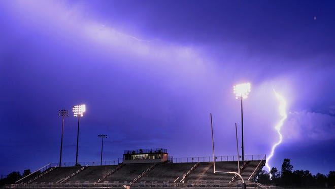 Lightning strikes after fans were evacuated  during heavy storms that delayed the Mason vs. Eaton Rapids football game in Mason.  Picture taken Friday September 5, 2014 .   (Rod Sanford | Lansing State Journal)