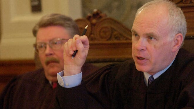 Presiding Justice, Glen Severson asks a question of lawyer Neil Fulton as justice John Bastian looks on while hearing oral arguments at the South Dakota Supreme Court in 2013