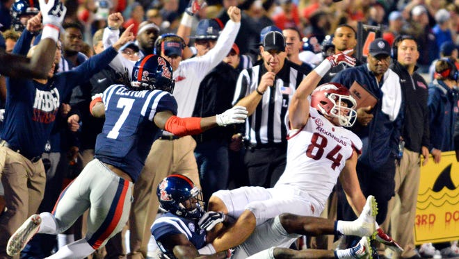 Arkansas tight end Hunter Henry laterals the ball as he is tackled by Ole Miss defensive back Tony Bridges during overtime at Vaught-Hemingway Stadium. Arkansas won 53-52.