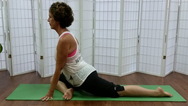 Anna Withrow of Yoga Bird, Fort Myers, moves into Pigeon Pose.