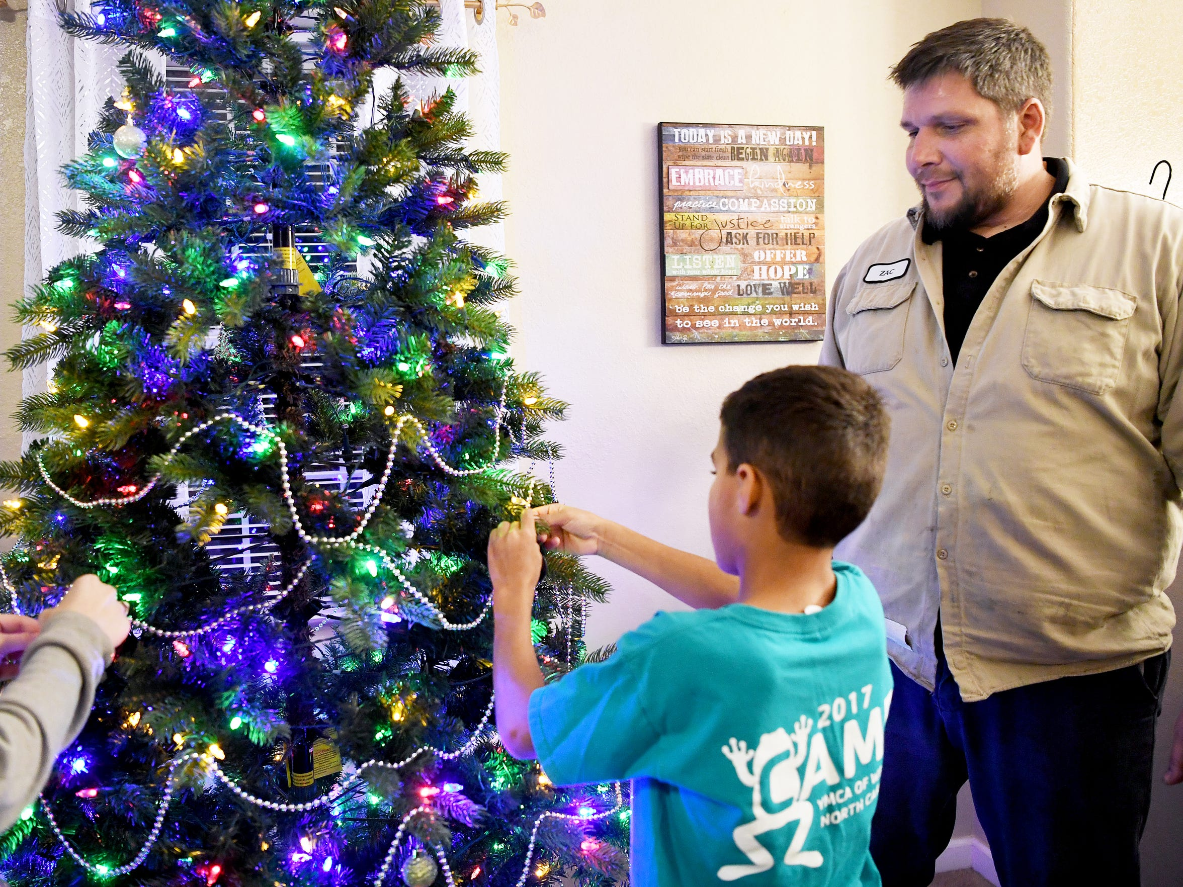 Zack Wyatt watches as Emanie, a foster child in his care, helps decorate the Christmas tree November 30, 2017.