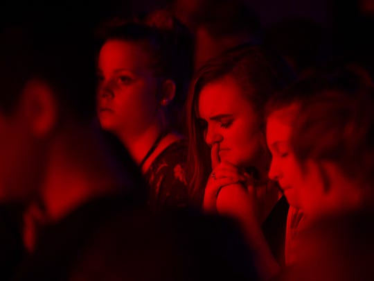 Madison Coffey, 15, closes her eyes as she listens
