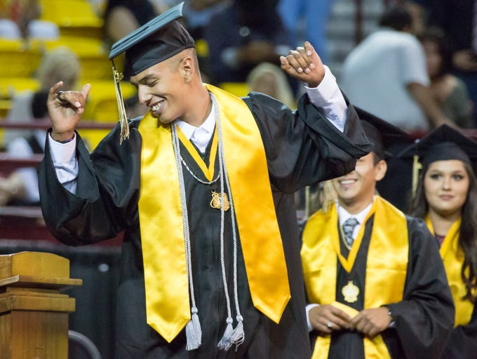 Graduate Victor Carreon dances on stage as he prepares