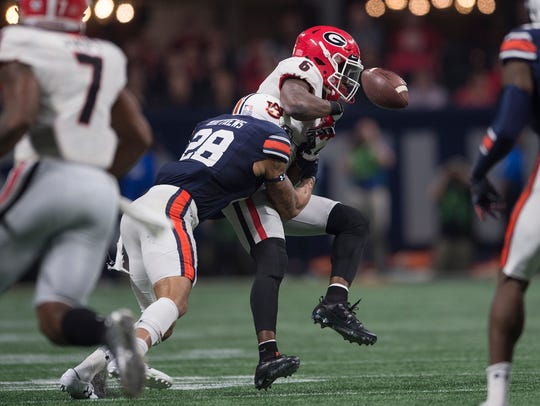 Auburn defensive back Tray Matthews (28) hits Georgia