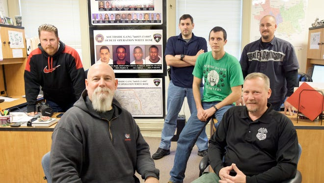 York City Narcotics Squad members, from left, Detective Scott Nadzom, Detective First Class Andy Shaffer, Officer Stephen Aderhold, Officer Zach Pelton, ATF Special Agent Scott Endy and Detective Bart Seelig, pose in their headquarters in an old York City fire station. The poster on the wall references the Southside Gang whose members are facing federal prosecution due to the efforts of the group. (Bill Kalina - The York Dispatch)
