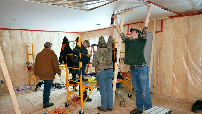 Technical High School students finish drywalling the living room in a home they are building Wednesday, Jan. 20. When finished the home will be sold by Central Minnesota Habitat for Humanity to a local, low-income family.