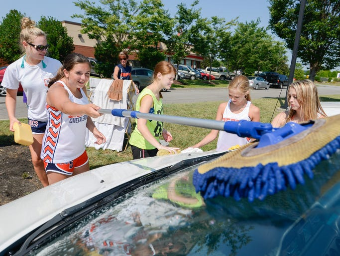 Beech High School freshman Ciara White makes a windshield shine as junior Kristina Gibbs works alongside her during a car wash to support the Beech High School Competition Cheerleading Squad in Hendersonville on Saturday, July 27.