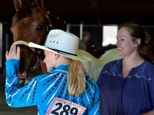 Ciara Ewald strokes the nose of her horse as they rest in between halter classes at the Manitowoc County Expo on Sunday, May 29. Behind her, Heidi Schiefelbein holds the horse's lead and talks with Ciara, who is her boyfriend's daughter, about the upcoming class.