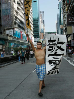 """A pro-democracy protester carries a banner that reads: """"bad police"""" down an occupied section of the Mong Kok district in Hong Kong, Friday, Oct. 17."""