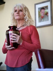 Mary Beth Cichocki holds an urn with the ashes of her 37-year-old son, Matt Klosowski, who overdosed from opiate drugs in January 2015.