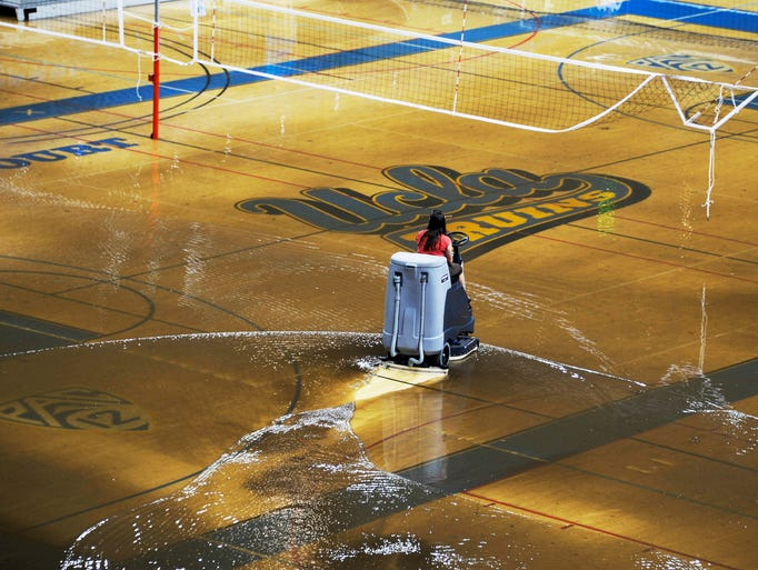 A worker begins the task of cleaning up at least an inch of water covering the playing floor at Pauley Pavilion, home of UCLA basketball.
