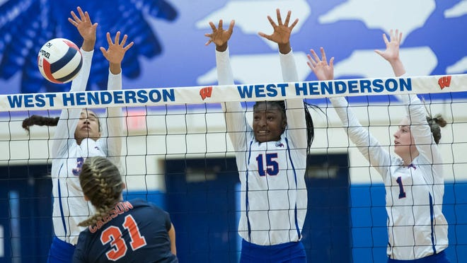 West Henderson's America Anderson (30), Daija Jackson (15), and Kinsley Morgan work together to block a hit against Jesse Carson in the second round of the 3-A state playoffs last season at West.