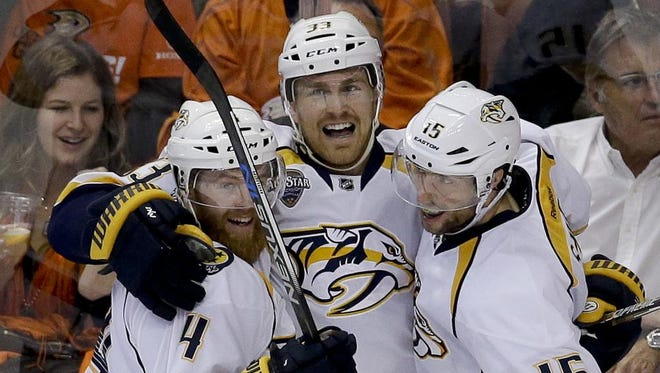 Predators center Colin Wilson, middle, celebrates with defenseman Ryan Ellis, left, and center Craig Smith after Wilson scored during the second period against the Anaheim Ducks.