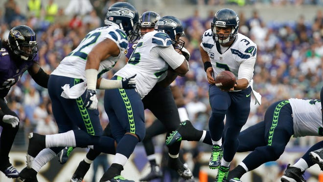 Seattle Seahawks quarterback Russell Wilson (3) prepares to hand off the ball during an NFL football game against the Baltimore Ravens, Sunday, Dec. 13, 2015, in Baltimore.