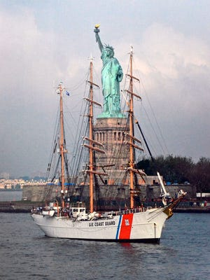 U.S. Coast Guard Cutter Eagle training vessell anchored in front of the Statue of Liberty.