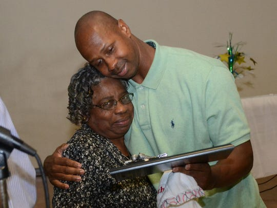 Retired major leaguer Juan Pierre hugs his mother, Derry, after she and his father, James, and siblings gave him a present at a retirement celebration for him in 2015 at St. Juliana Catholic Church.