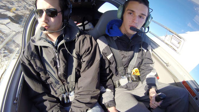 Jason Green, right, who flies with instructor Dan Olsson in a recent instructional flight, completed his solo flight during his senior year at Howell High School.