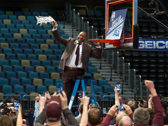 Montana head coach Travis DeCuire cuts down the net