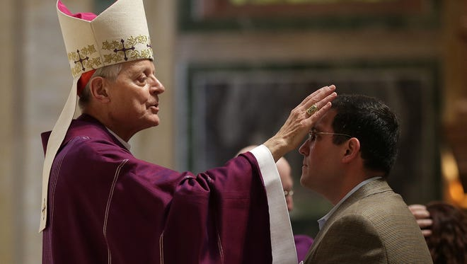 Cardinal Donald Wuerl places ashes on the foreheads of Catholics during Ash Wednesday Mass at the Cathedral of St. Matthew the Apostle Feb. 18, 2015 in Washington, DC.