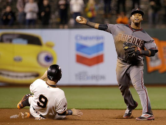Arizona Diamondbacks second baseman Jean Segura, right, throws to first base after forcing out San Francisco Giants' Brandon Belt (9) at second base on a double play ball hit by Brandon Crawford during the eleventh inning of a baseball game in San Francisco, Monday, April 18, 2016. The Diamondbacks won 9-7 in 11 innings. (AP Photo/Jeff Chiu)